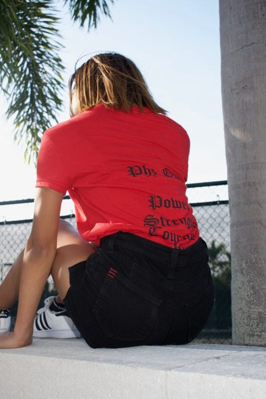 girl sitting on rooftop by palm tree and red t-shirt and black shorts
