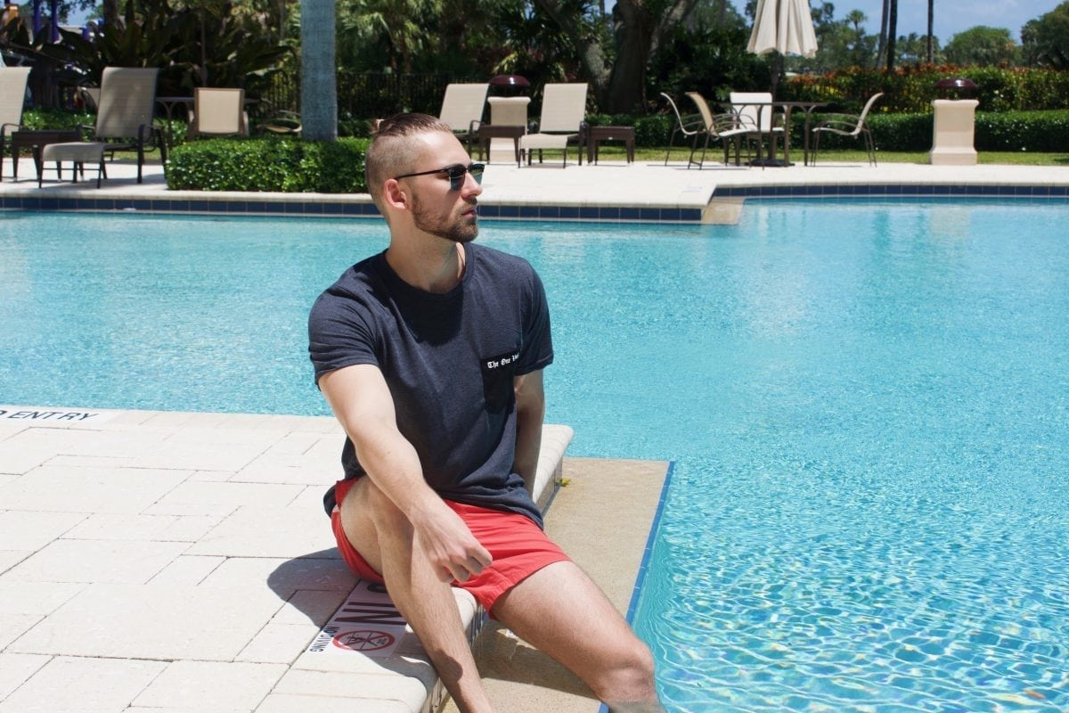 guy sitting by poolside in grey pocket tee and sunglasses